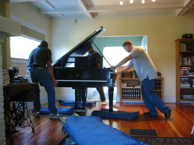 Piano is moved to its place in room